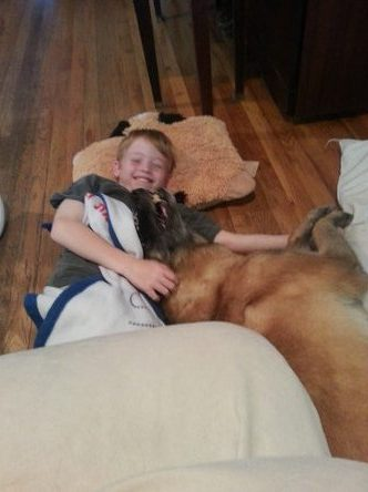 Little boy laying down and laughing with his dog